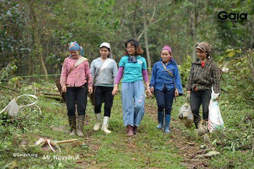 Cán bộ Gaia và người dân hàn huyên khi di chuyển tới địa điểm trồng rừng khác
