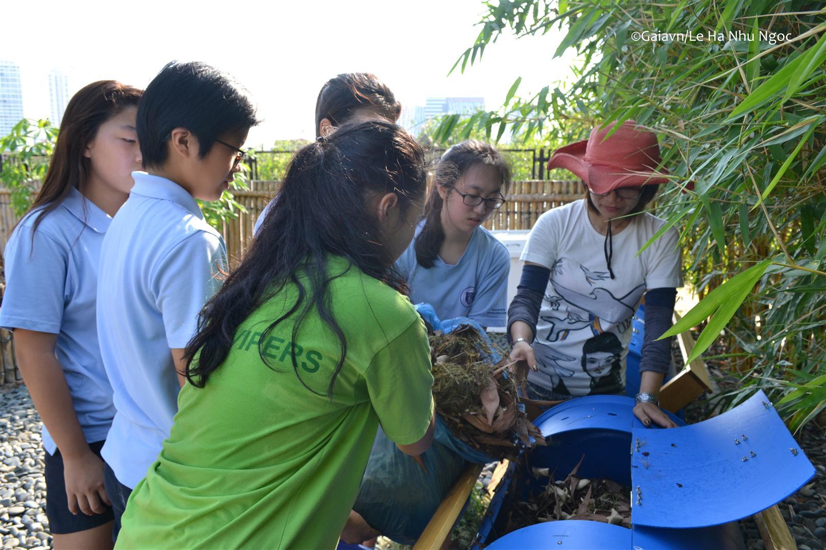 Học sinh đổ nguyên liệu vào thùng compost